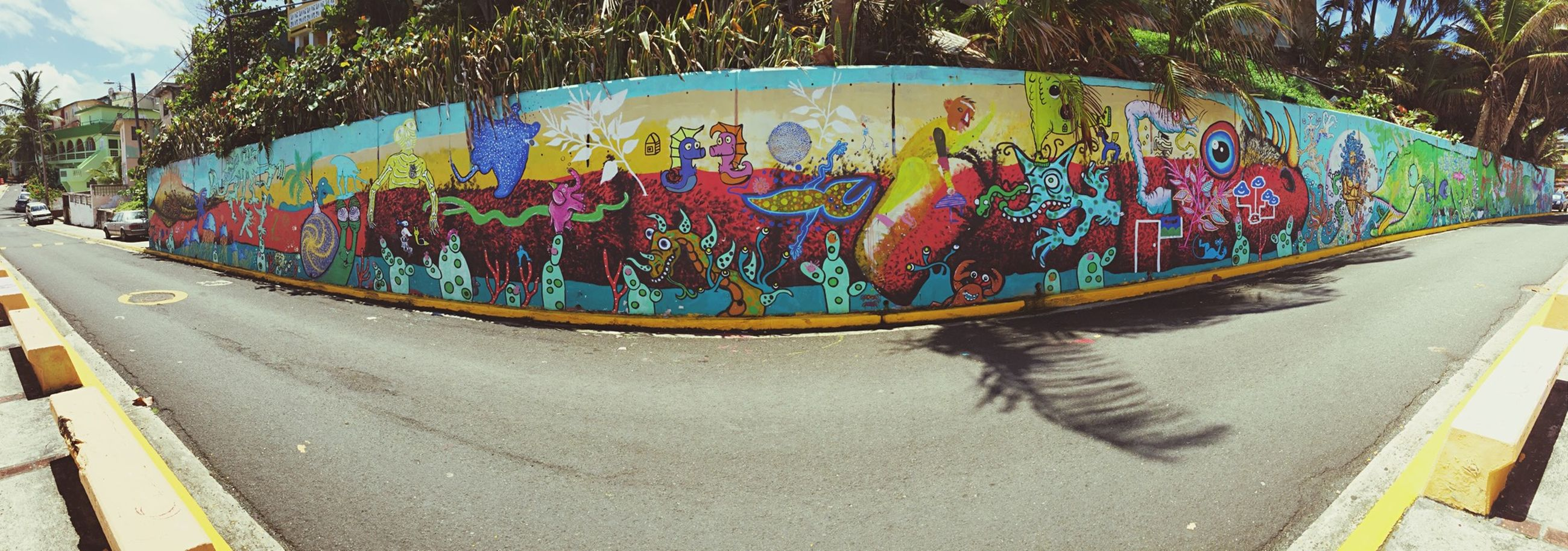 street, road marking, road, transportation, graffiti, art, text, multi colored, art and craft, tree, creativity, the way forward, city, asphalt, sidewalk, outdoors, building exterior, day, car, built structure
