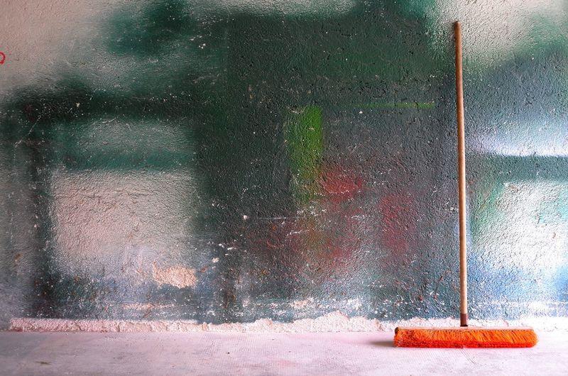 Orange broom against painted wall