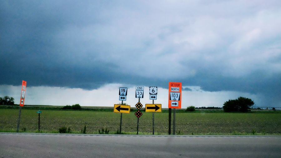Road Signs On Field Against Sky