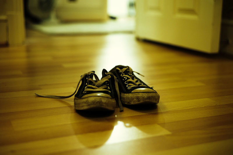 Close-up of dirty shoes on floor at home