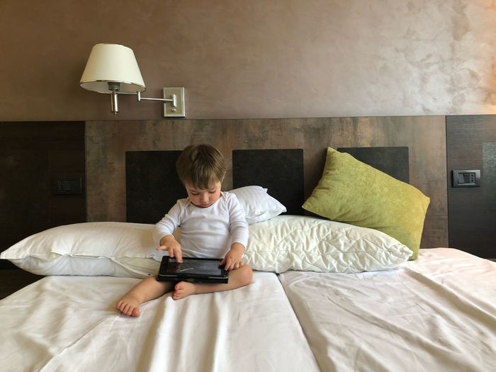 Full Length Of Boy Using Digital Tablet While Sitting On Bed At Home