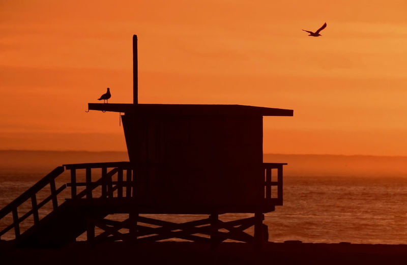 Silhouette Lifeguard Hut At Beach Against Sky During Sunset
