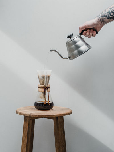 Cropped hand pouring coffee in container
