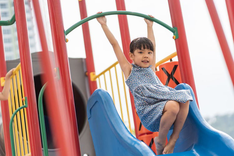Asian girl playing at playground Boys Casual Clothing Child Childhood Front View Innocence Jungle Gym Leisure Activity Lifestyles Males  Men One Person Outdoor Play Equipment Playground Playing Real People Sitting Slide Slide - Play Equipment