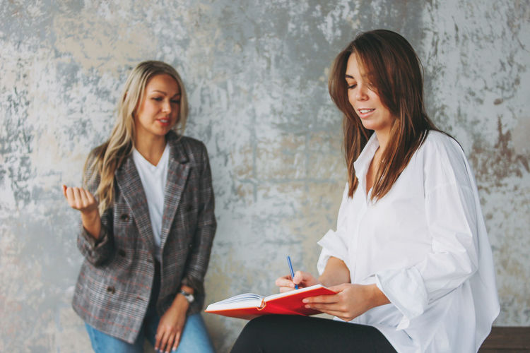 Businesswoman writing in diary while discussing with coworker in office