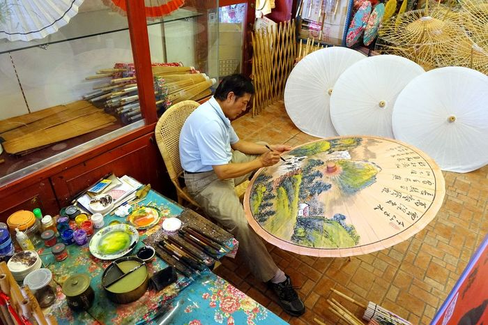 An artist paints a Chinese traditional bamboo oil paper umbrella Artist Bamboo Chinese Culture Landscape Painting Male Artist Paintbrush Painter Skillful Traditional Art Umbrella