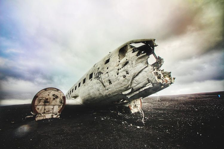 Abandoned Airplane On Beach Against Cloudy Sky
