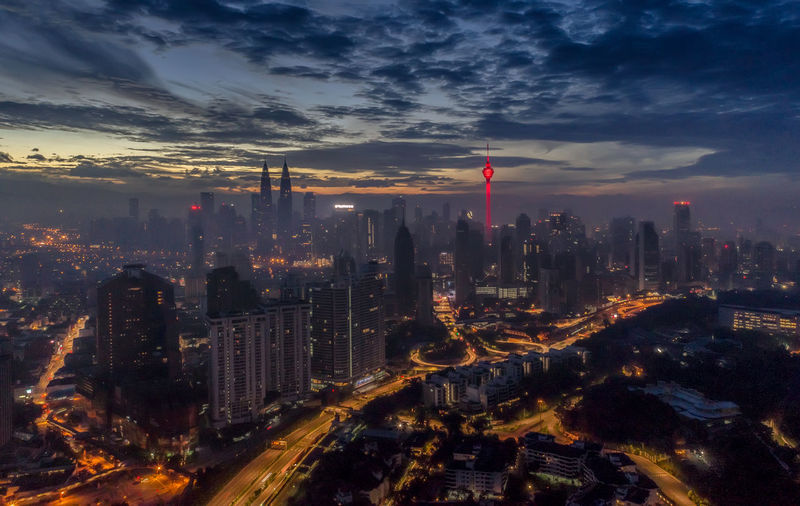 Aerial view of city lit up against cloudy sky