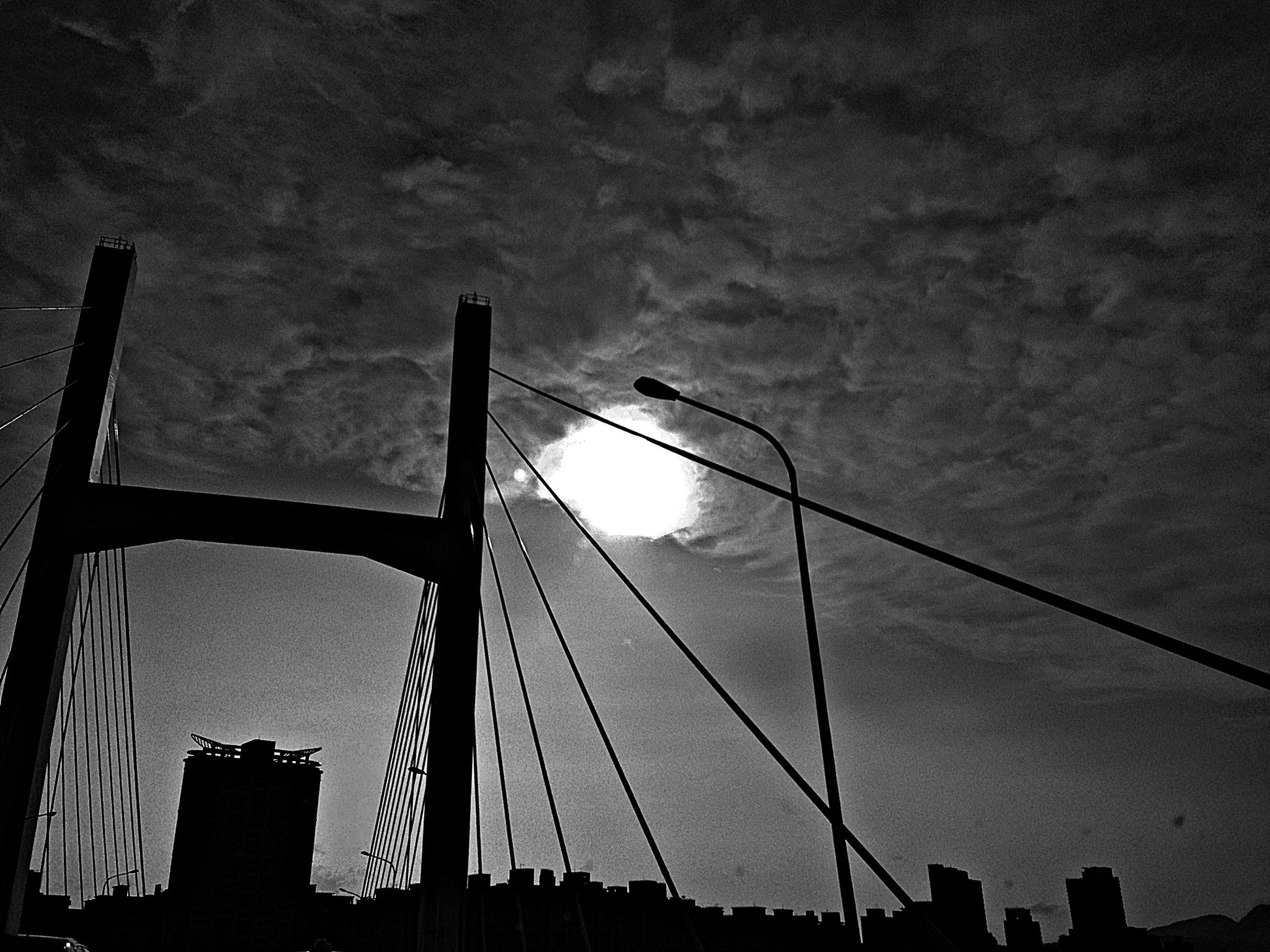 low angle view, built structure, architecture, silhouette, sky, street light, building exterior, connection, sunset, city, dusk, cloud - sky, outdoors, building, no people, bridge - man made structure, lighting equipment, cloud, tall - high, high section