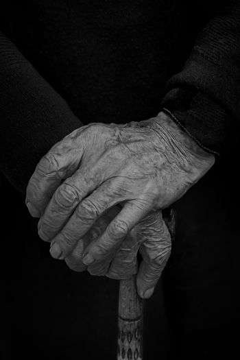 Cropped hands of senior person holding walking cane against black background