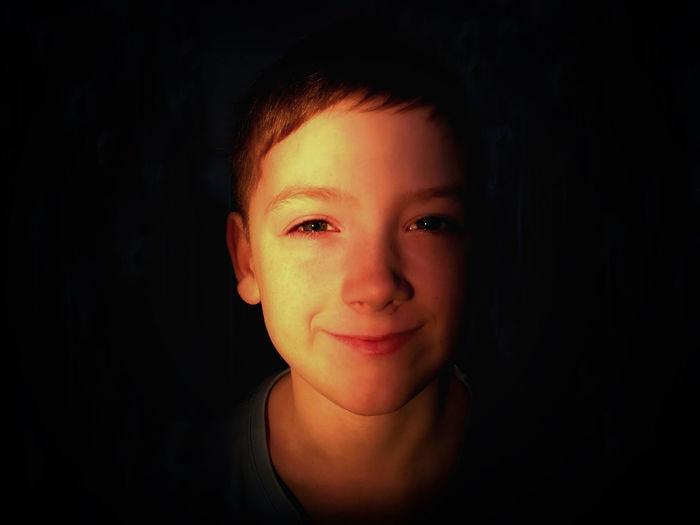 Close-up portrait of boy against black background
