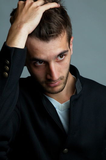 Close-up of thoughtful young man over gray background