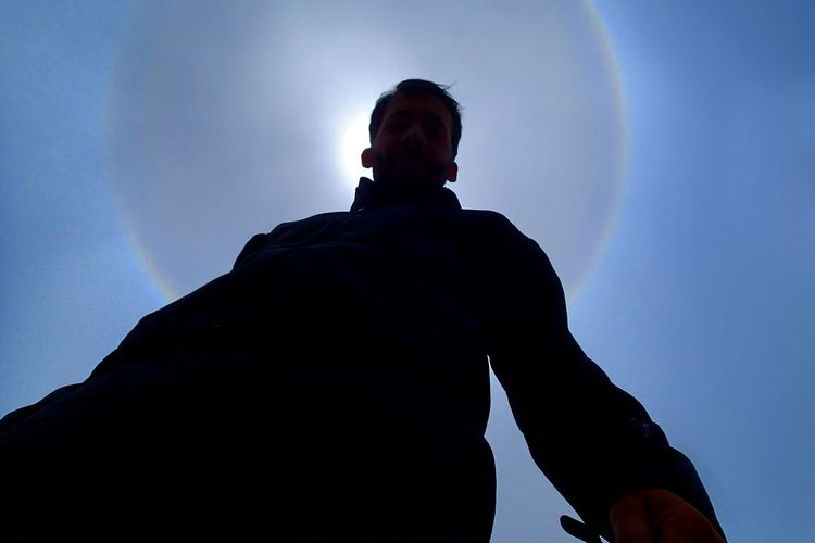 Low angle view of man looking against blue sky