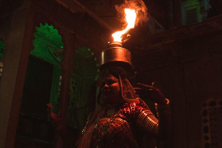 Portrait of woman holding lit candles