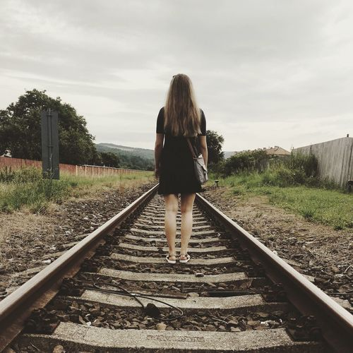 Rear view of woman standing on railway tracks against sky