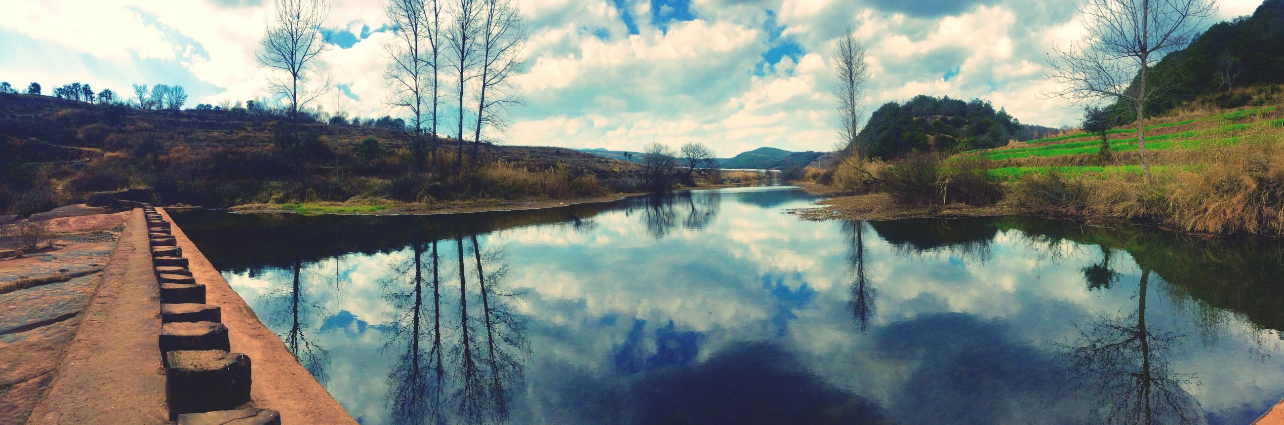sky, reflection, water, lake, tranquil scene, tranquility, cloud - sky, scenics, mountain, beauty in nature, cloud, nature, tree, standing water, blue, panoramic, cloudy, mountain range, river, idyllic