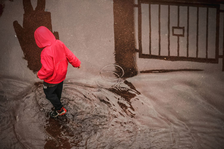 One Person Childhood Child Real People Full Length Red Lifestyles Standing Leisure Activity Clothing Day Motion Nature Winter Architecture Rear View Boys Built Structure Warm Clothing Innocence Wet Water Reflection Puddle Inondation Game Get Your Feet Wet Feet Shadows Getting Wet