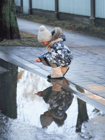 Reflection of boy in puddle