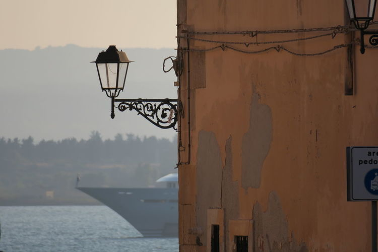 A ship on the corner (Ortigia, Jul 2018) Ph. Valerio Corzani Sicily Sicily ❤️❤️❤️ Architecture Building Building Exterior Built Structure Day Electric Lamp Focus On Foreground Lamp Lighting Equipment Metal Nature Navy No People Ortigia Ortigiabedda Ortigiaisland Outdoors Sky Street Street Light Technology Wall - Building Feature Water