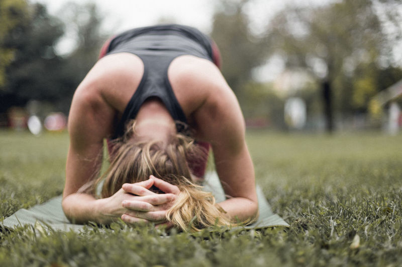 Woman practicing headstand on grassy field