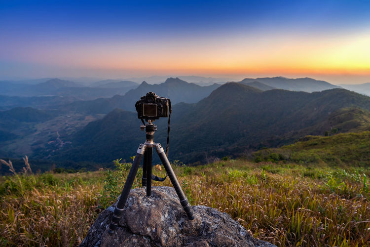 Digital camera on tripod in the mountains. Mountain Scenics - Nature Mountain Range Tripod Environment Beauty In Nature Sky Photography Themes Technology Nature Tranquil Scene Landscape Non-urban Scene Camera - Photographic Equipment Tranquility Land No People Photographic Equipment Grass Sunset Outdoors Digital Camera Mountain Peak