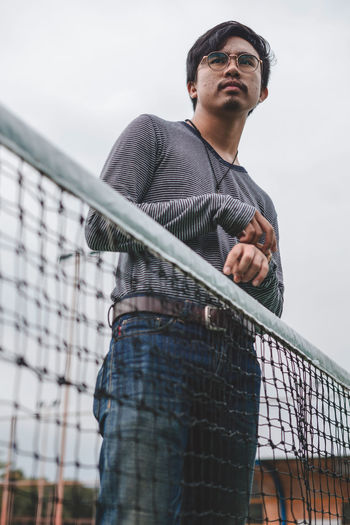 Low angle view of man by net standing against sky