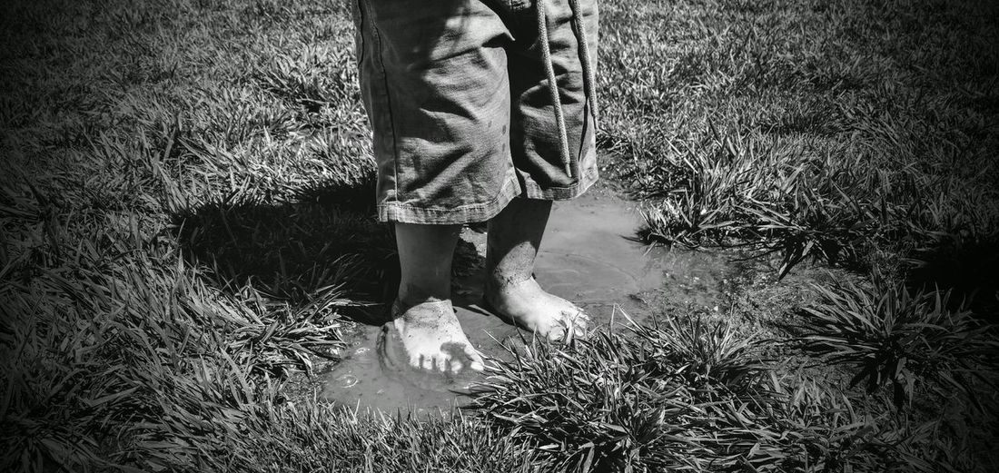 Low section of boy standing in muddy water