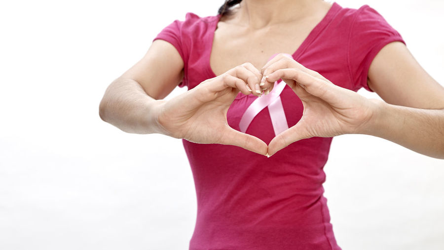Midsection of woman with cancer awareness ribbon making heart shape over white background