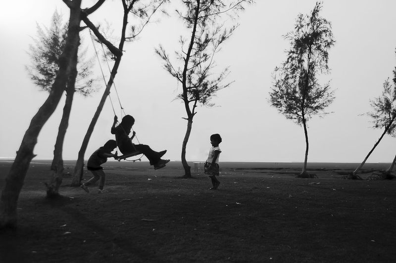 Children playing on playground against sky