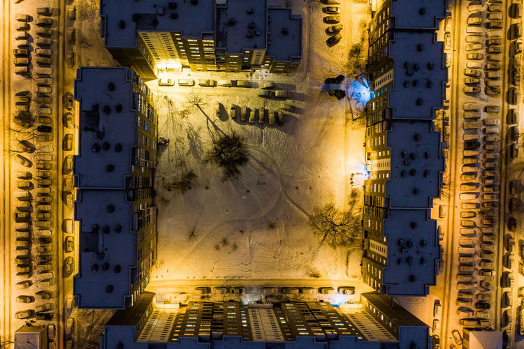 Drone view of illuminated buildings in city at night during winter