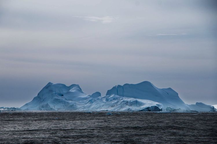 Scenic view of iceberg by sea against sky