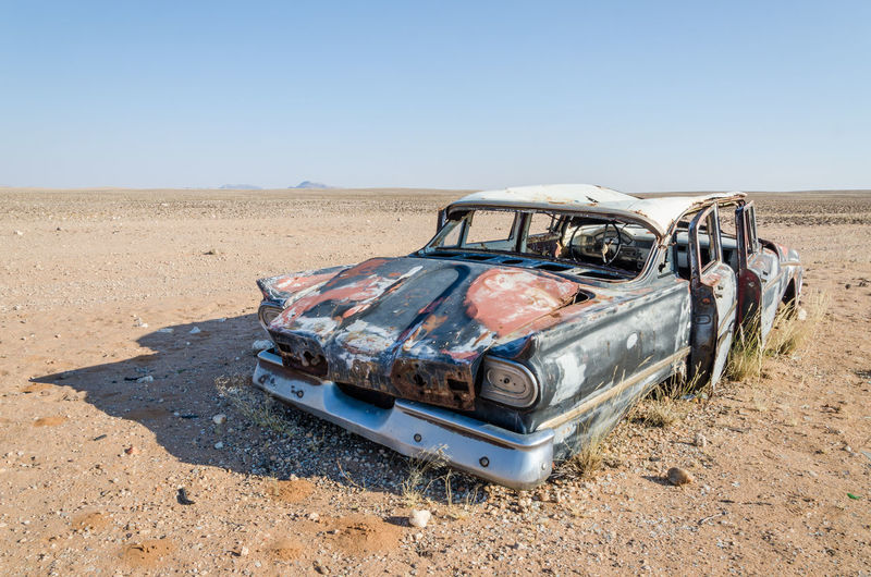 Wreck of abandoned vintage car against clear blue sky in namib desert of angola, africa