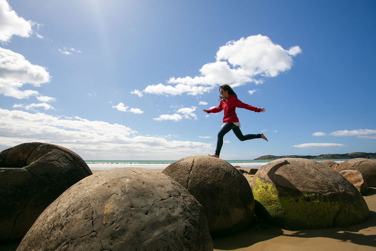 Woman Jumping Over Rocks At Beach Against Sky