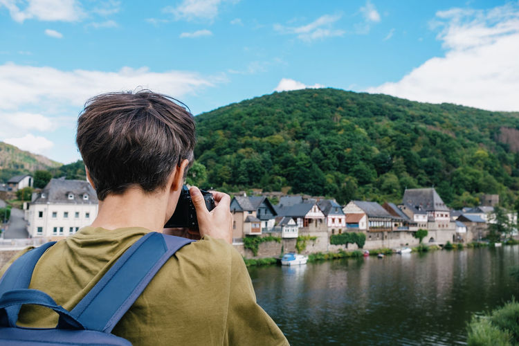 Rear view of man photographing houses against hill