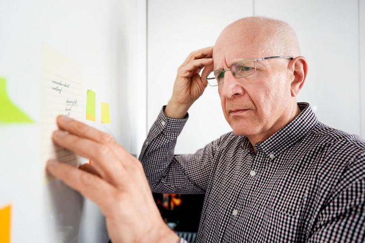 Senior man brainstorming while looking at adhesive note at home