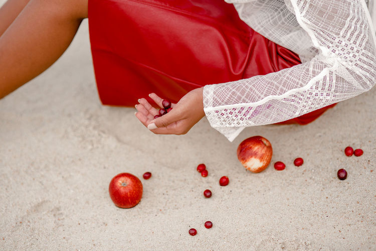 Midsection of woman holding fruit on sand