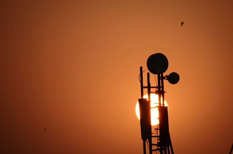 Low angle view of silhouette repeater tower against orange sky