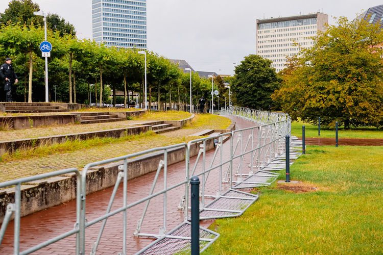 Footpath by trees in park against buildings in city