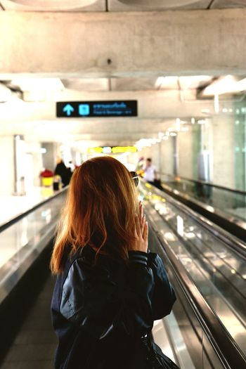 Woman Standing On Moving Walkway At Airport