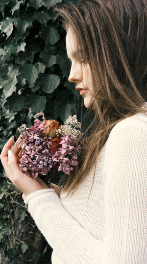Adult Beautiful Woman Beauty In Nature Brown Hair Close-up Flower Flower Arrangement Flower Head Flowering Plant Freshness Hair Hairstyle Holding Leaf Lifestyles Long Hair Nature One Person Outdoors Plant Plant Part Smelling Women Young Adult Young Women