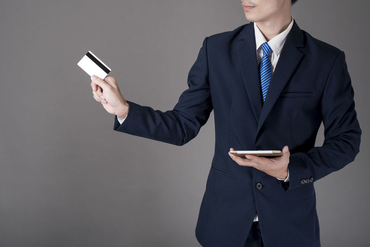 Low angle view of man holding mobile phone