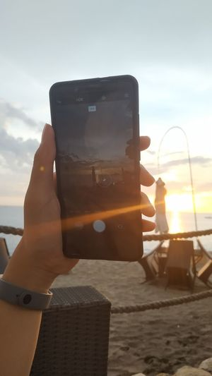 Person holding camera against sky during sunset