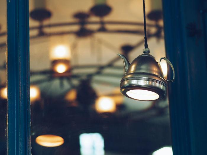 Close-up of illuminated pendant light hanging in darkroom