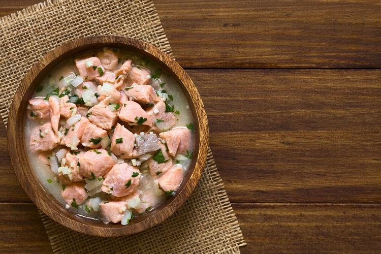 Chilean salmon ceviche prepared with onion, garlic, fresh coriander, salt and lemon juice, photographed overhead with natural light (Selective Focus, Focus on the top of the ceviche) Chile Chilean  Dish Homemade Homemade Food Meal Raw Snack South American Food Appetizer Cebiche Ceviche Chilean Food Cilantro Coriander Fish Food Food And Drink Fresh Lemon Onion Raw Food Salmon Salmon Ceviche Seafood
