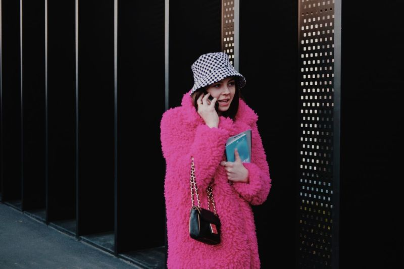 Woman standing against pink wall during winter