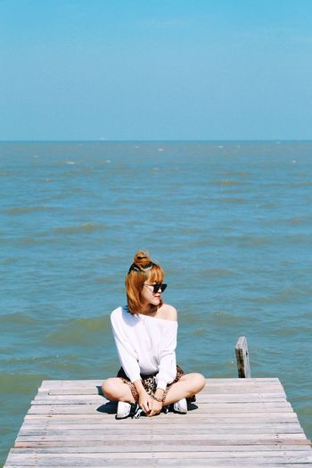 Woman sitting on pier by sea against clear sky