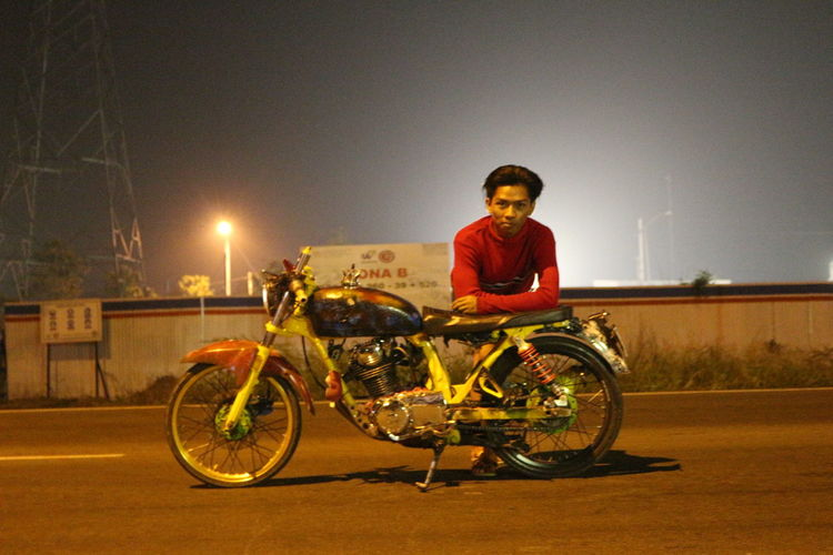 Portrait of man with bicycle on road against sky at night