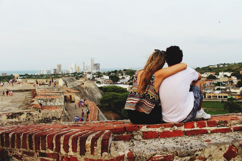 Rear view of couple sitting on retaining wall at castle against clear sky