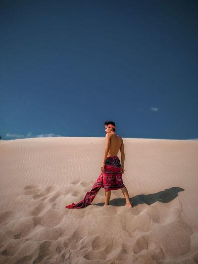 Full length of man on sand at beach against clear sky