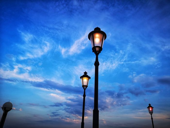 Low angle view of illuminated lamp posts against sky at dusk